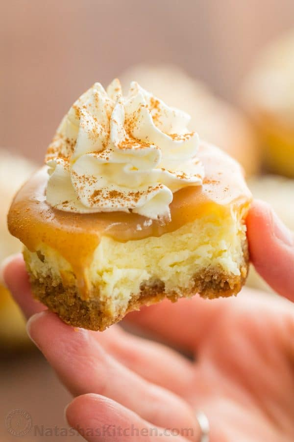 Mini Cheesecakes With Caramel Topping And Whipped Cream Sprinkled Cinnamon