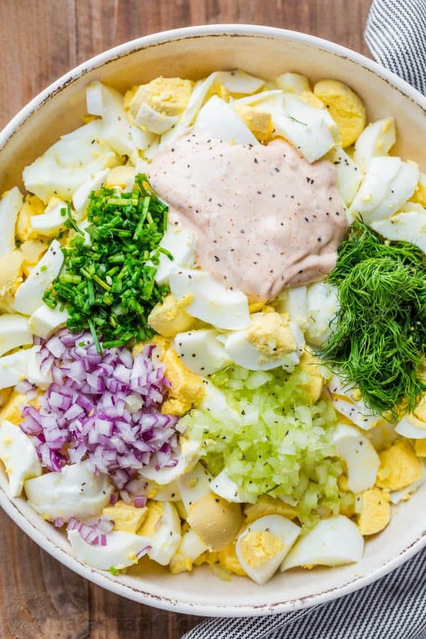 Boiled egg, onion, celery, dill salad ingredients diced in a bowl for egg salad.
