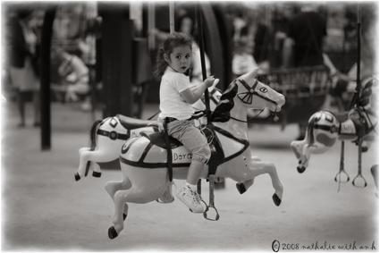 Little girl on wood horse