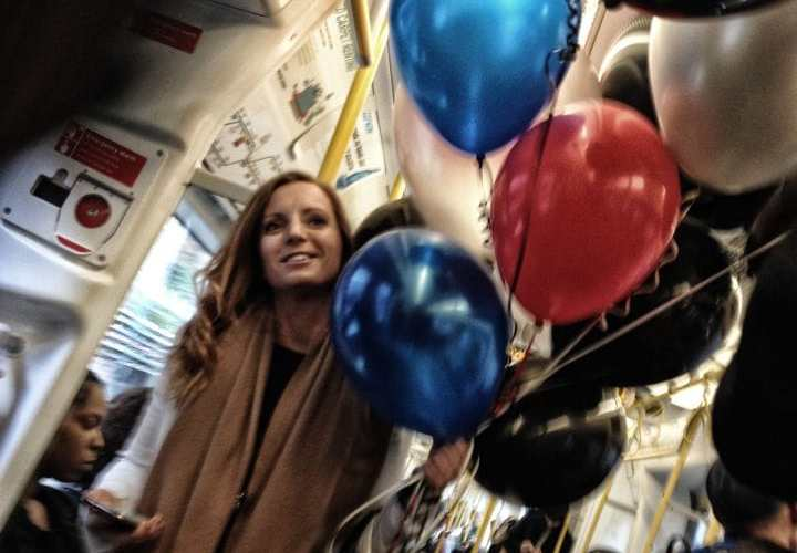Woman on London Underground with balloons