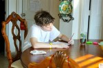 student doing homework on dining room table