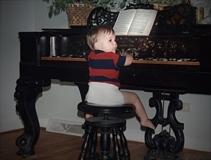 Nathan Shirley as baby playing piano square grand
