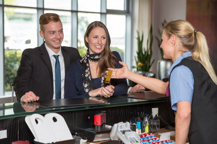 Hotel receptionist handing over key to customers