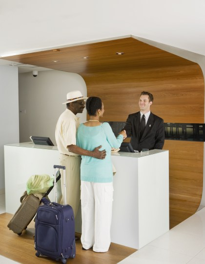 Senior African couple at hotel counter