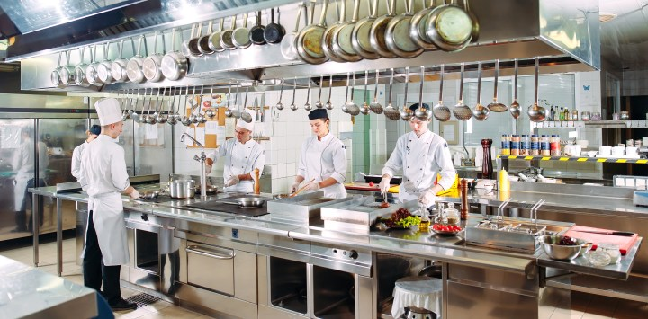 Chefs in a high end restaurant kitchen surrounded by expensive equipment.