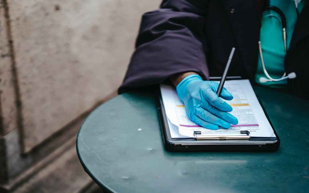 crop black doctor with document at table