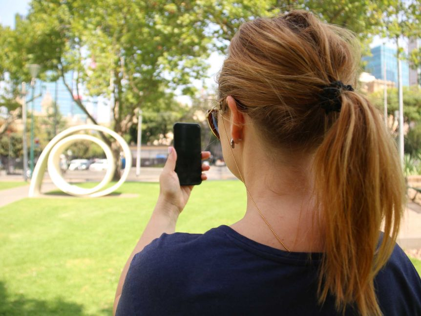 A woman sits in a park using her phone, her face is turned away from the camera.