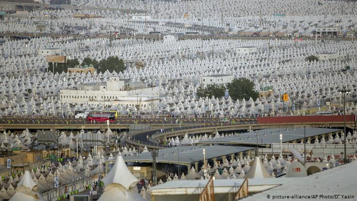 Muslim pilgrims walk back to their tents during the annual Haj pilgrimage on the first day of Eid al-Adha in Mina
