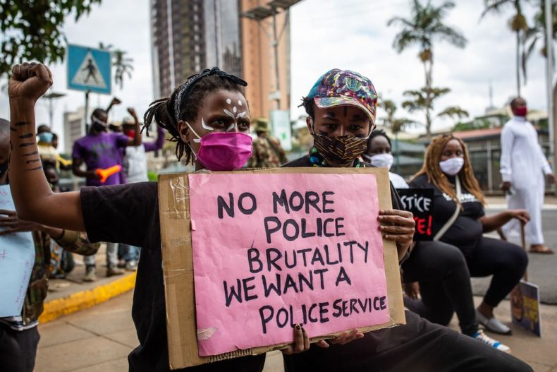Protesters hold placards in front of the Kenyan Parliament during their protest against police brutality in Nairobi on June 9, 2020. - Kenyan police have been involved in the killing of 15 people since the country put a nighttime curfew in place in March 2020 to combat the COVID-19 coronavirus, the policing oversight body said in a statement seen by AFP on June 5, 2020. (Photo by Patrick Meinhardt / AFP) (Photo by PATRICK MEINHARDT/AFP via Getty Images)