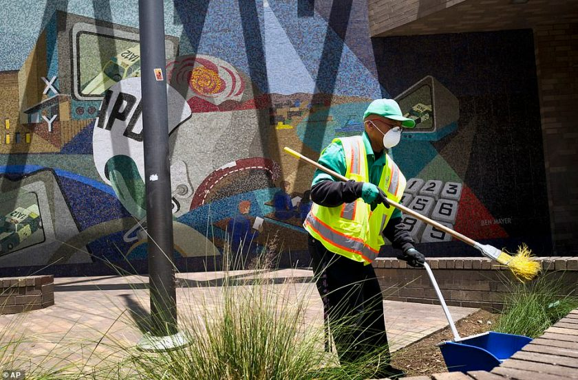 A cleaning crew sweeps up in front of LAPD Central Community Police Station in downtown Los Angeles on Thursday