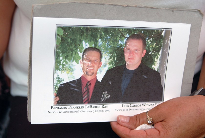 A woman holds a picture of Mormon anti-crime activist Benjamin LeBaron, left, and his in law Luis Widmar during their funeral