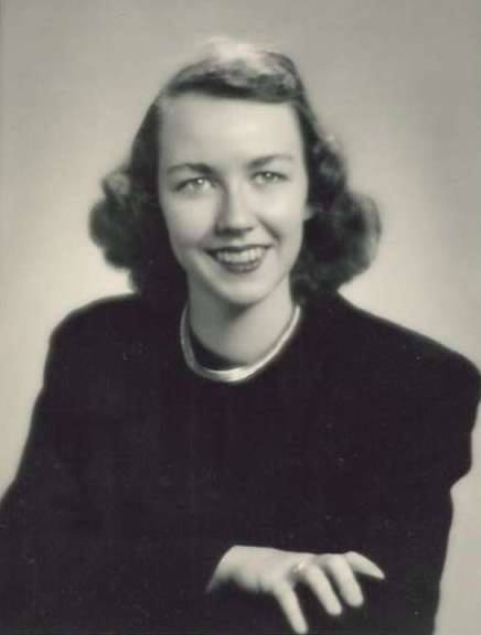 A portrait of Flannery O'Connor smiling and wearing a black dress