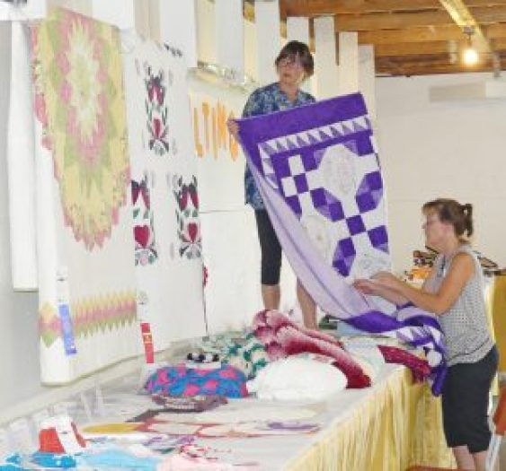 Checking through the quilt and sewn homecraft entries. Zandbergen photo, Nation Valley News