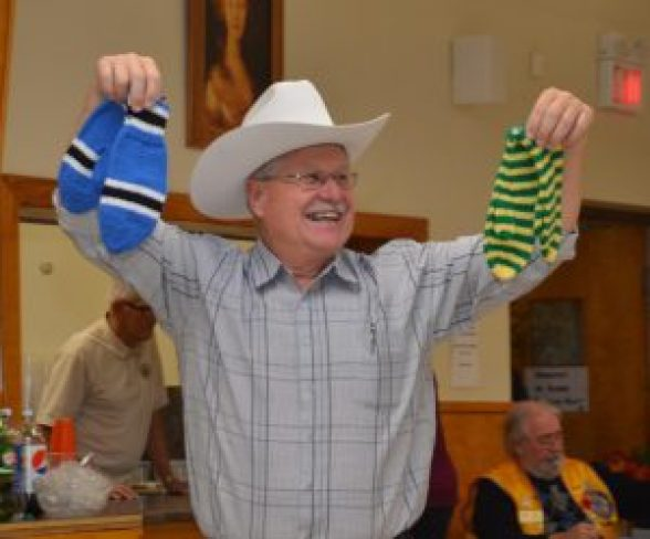Jack Barkley holds up donated knitted items on the auction block. Courtesy photo