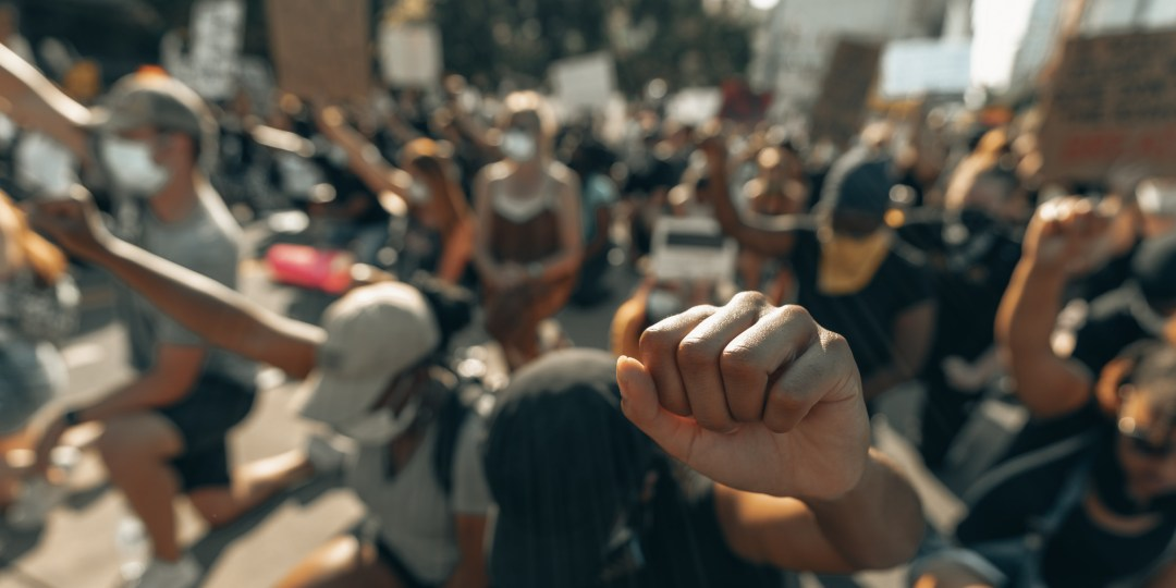 Many people raising their arms with a fist
