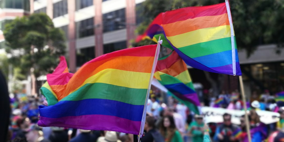 Two Pride rainbow flags being waved during the San Francisco Pride Prade