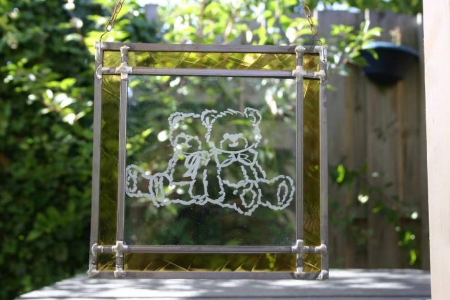 Glas in lood raamhanger met gegraveerde beren in het midden, rand is van geel glas.
