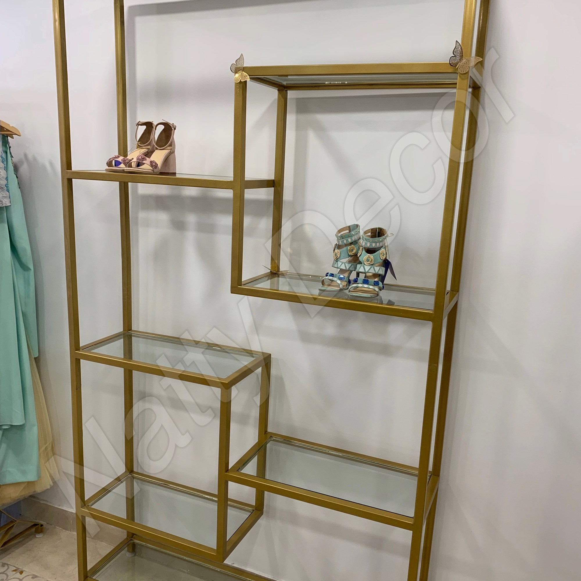 A tall golden glass rack for displaying designer concepts in stores