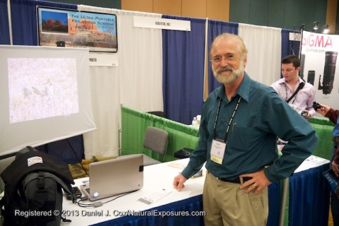 Barry Walton at his booth showing off his new ultra portable projection screen.