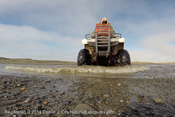 Denver Holt rides his four wheeler across the mouth of salt water estuary along the coast of the Beaufort Sea. Individual still frame taken from video from GoPro Black Edition.