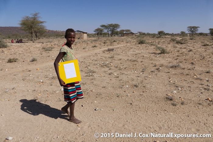 A young Samburu girl shows how easy it is to carry her new Outpostz Lap Desk to and from school. Kenya