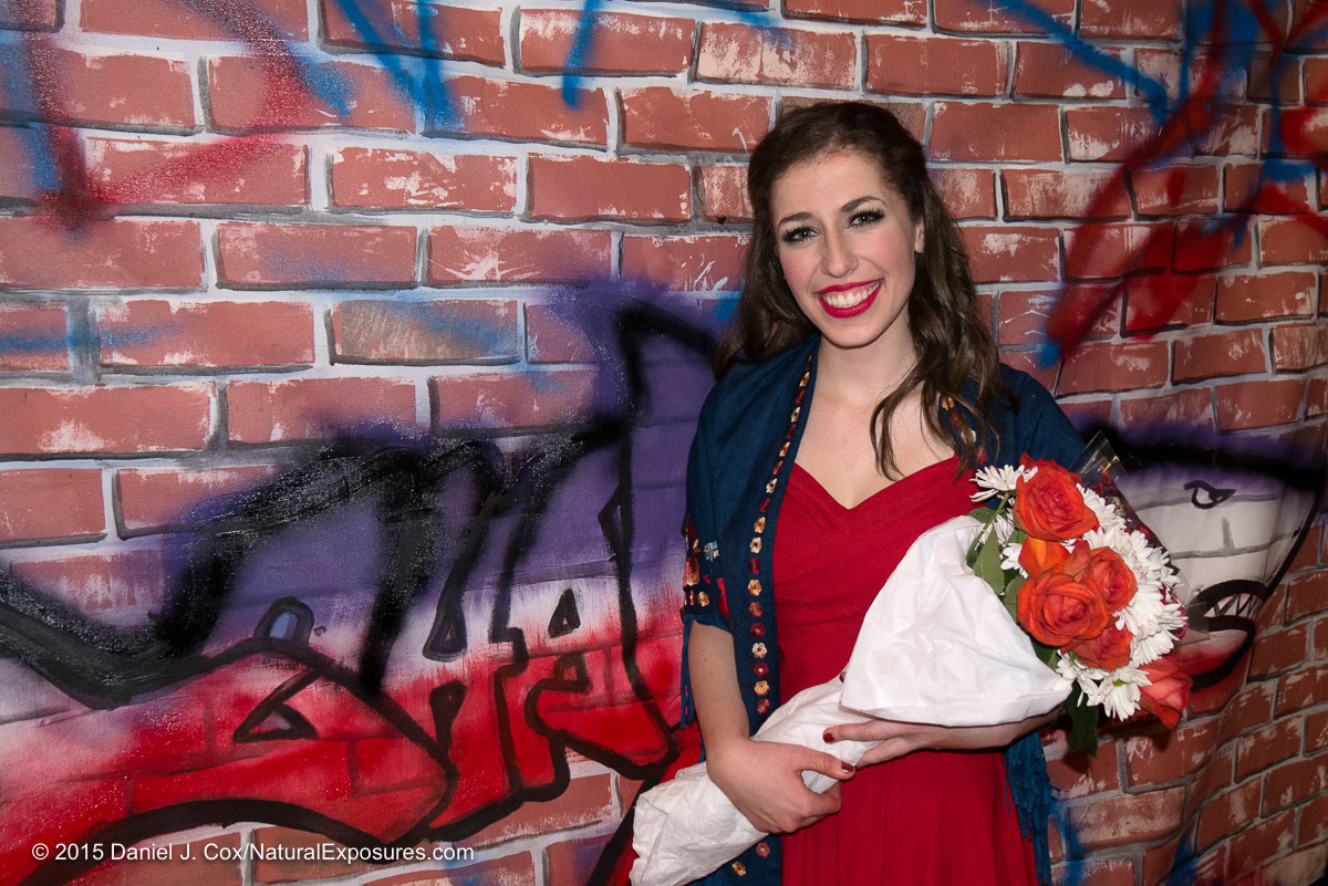 Olivia poses with her flowers against the backdrop of the Sharks wall on stage. I put Olivia against the background after the performance so add some color and an important element of the play. Lumix G7 with 14-140mm. On camera flash. ISO 800