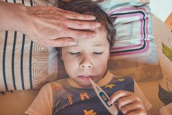 little boy with a thermometer in his mouth with mother's hand on his forehead making sure he does not have a fever