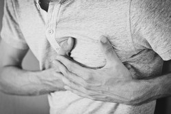 man holding his chest in pain due to angina