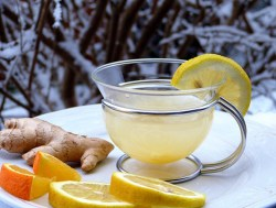 cup of lemon tea with lemon garnish, ginger, sliced oranges and lemons all representing a foods for a strong immune system