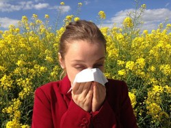 woman in red shirt blowing her nose due to allergies with yellow flowers in the background