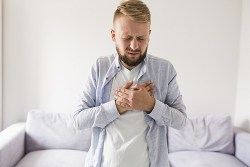 man holding his chest in pain with both hands due to a hiatal hernia attack
