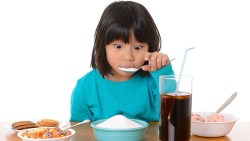 child eating a plate of sugar with all types of sugary snacks and drinks on the table