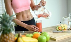 incredible fit woman pouring juice into glass surrounded by multiple fruits and vegetables she used for juicing for weight loss