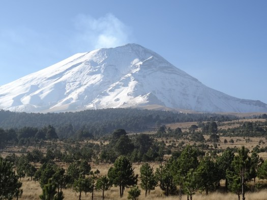 Photo showing the snow covered, smouldering volcano