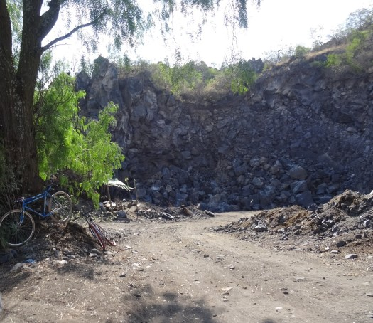 Photo showing a dirt track leading to an open rock face shrouded in boulders and stones from the quarrying process