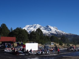 Photo showing a fiesta in a car park, with the volcano centred in the background