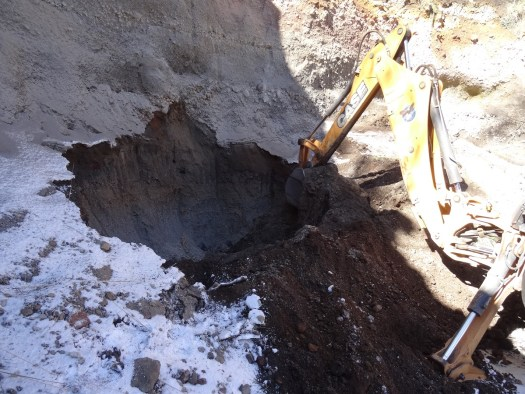 Photo showing the excavator living a pile of soil away from the face of a hillside to create a hole.