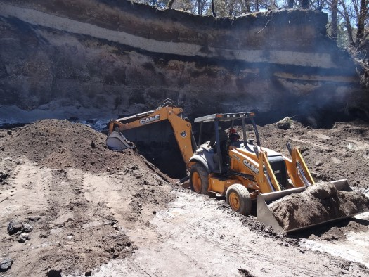 Photo showing the excavator at the hillside with soil piled to left and right but the hole no bigger