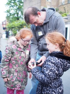 Two young girls and their dad gather round a bat detector