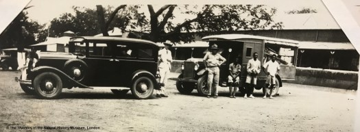 Black and white archival photograph showing two vehicles with men stood beside them, one man in a white suit and hat to the left, and a group of 4 men to the right.