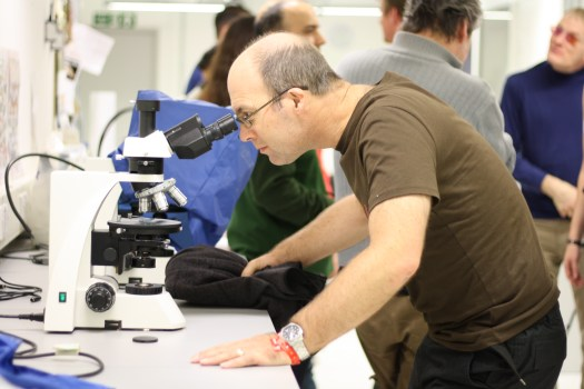 Photo showing a man with glasses leaning forward to peer into the lens of a light microscope
