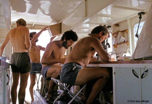 Colour archival photograph showing four bare-chested men in shorts seated and standing inside the mobile laboratory in the truck.