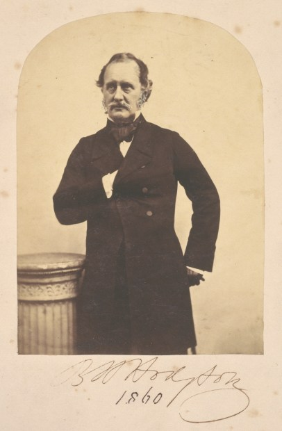 Sepia photograph showing Brian Houghton Hodgson standing, from the knees upwards, facing the photographer, but looking slightly to the right. He is standing next to a light coloured decorative column , which comes up to his waist. He is dressed in a stand calf length dark Victorian plain dress coat, buttoned once in the middle. His right hand is resting inside the breast opening of the coat, with just his white shirt cuff visible. His left hand is resting on his hip. He is wearing a dark gentleman's neck scarf. He has light coloured, probably grey moustache and side burns and short hair, brushed back from his forehead. He shows no emotion on his face. The background is light and plain.