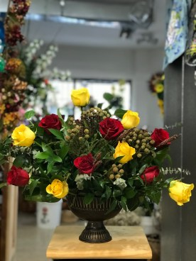 LVRE028-Red and Yellow Roses with a rustic bronze vase.