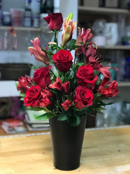 LVRE019-Red roses . red lilies and red astromelias in an elegant black ceramic vaseSpecial: $58.00