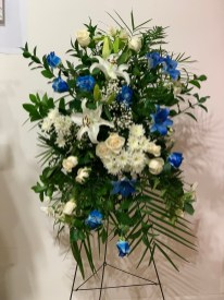 FNR018 Spray arrangement with blue roses, white Lillies and white cushion. $280.00