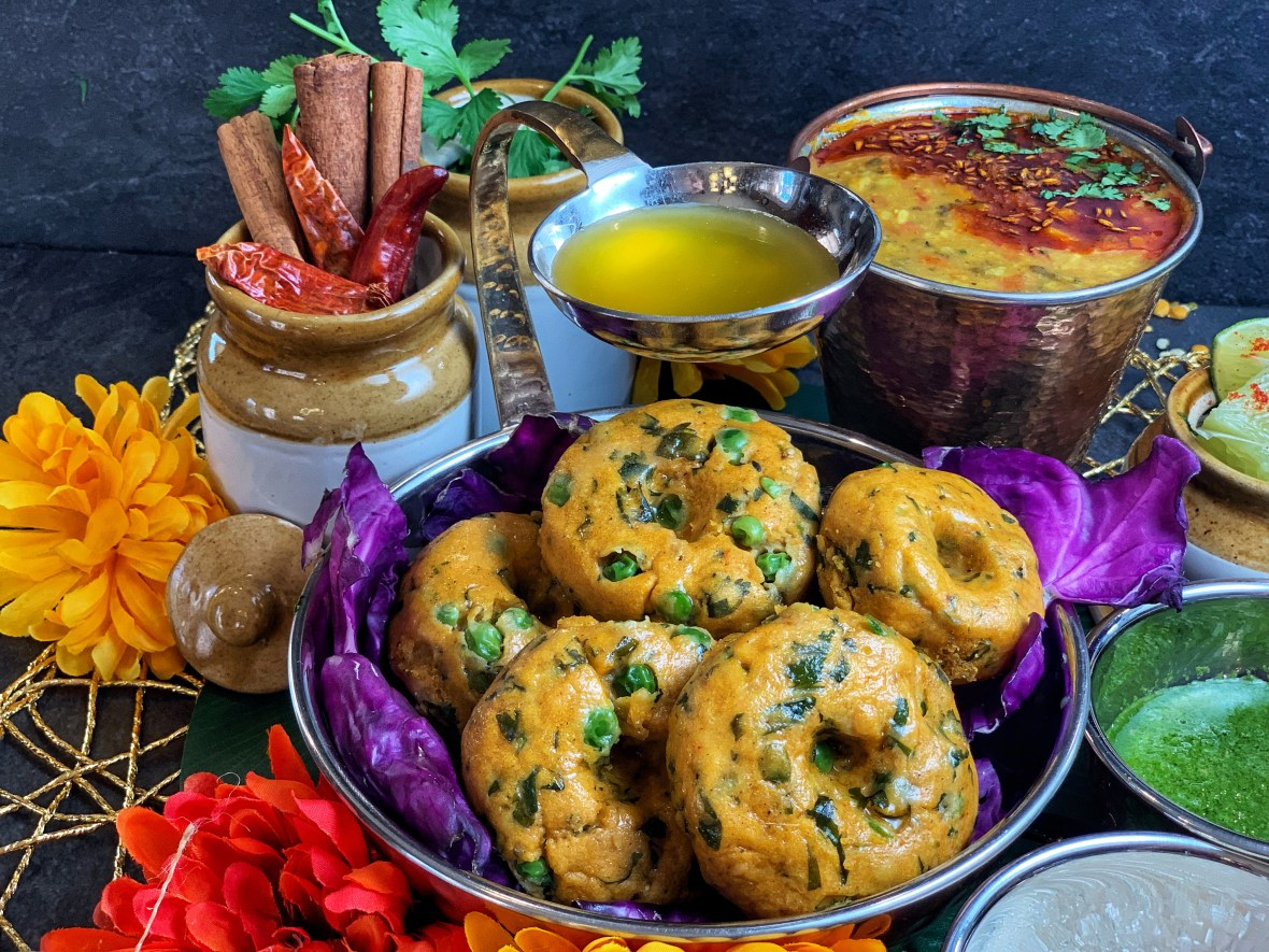 Makki ka Dhokla with Spicy Moong Dal (Steamed Corn Cakes with Moong Lentil Stew) - the quintessential Rajasthani dish! Try these steamed corn cakes with peas and methi (fenugreek) leaves and spicy, protein rich moong dal, chutney and ghee, for a wholesome, finger-licking meal this winter!