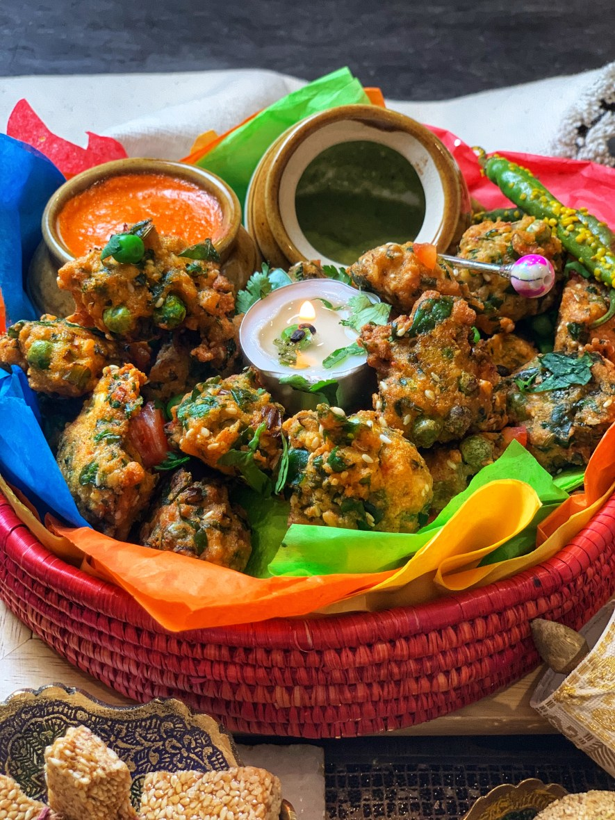 Moong Dal Pakodas (lentil fritters) is a traditional dish that I have been enjoying since my childhood on Makar Sakranti, the kite festival. Savor it with freshly made chili-garlic and cilantro-mint chutney! It's crisped to perfection and a festive, texture-filled way to beat the weather!