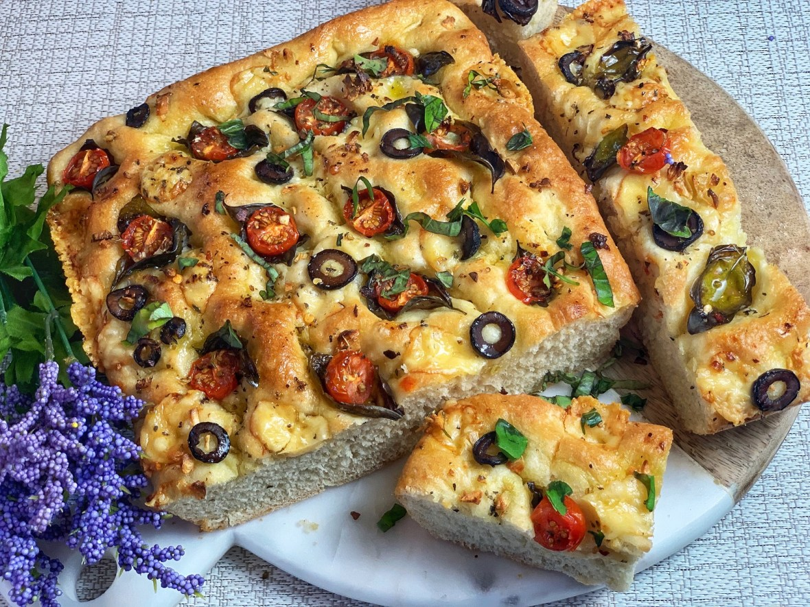 Tomato Basil Focaccia — a comforting, spongy Italian bread baked with fresh tomatoes, olives, aromatic basil, garlic, herbs, and melted cheese. A simple recipe with restaurant quality results, this focaccia is a delicious treat, waiting for you to indulge!