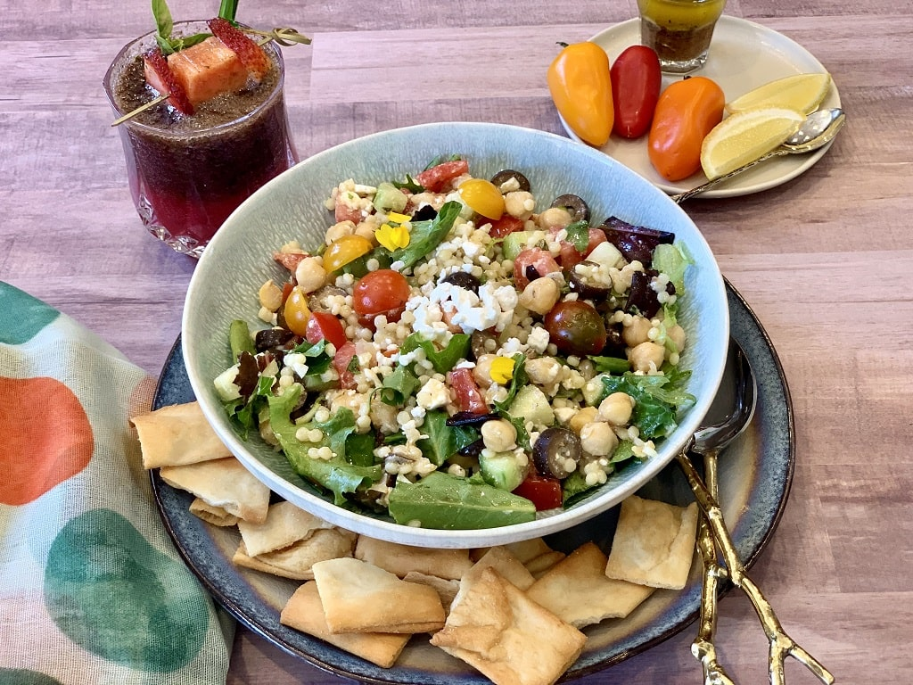 Greek Couscous Salad featuring chickpeas, cucumber, tomatoes, feta, and a drizzle of red wine vinaigrette. This Mediterranean salad full of protein is perfect for a refreshing, balanced lunch.
